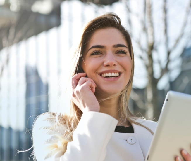 A business woman smiling on the phone while holding onto an iPad.