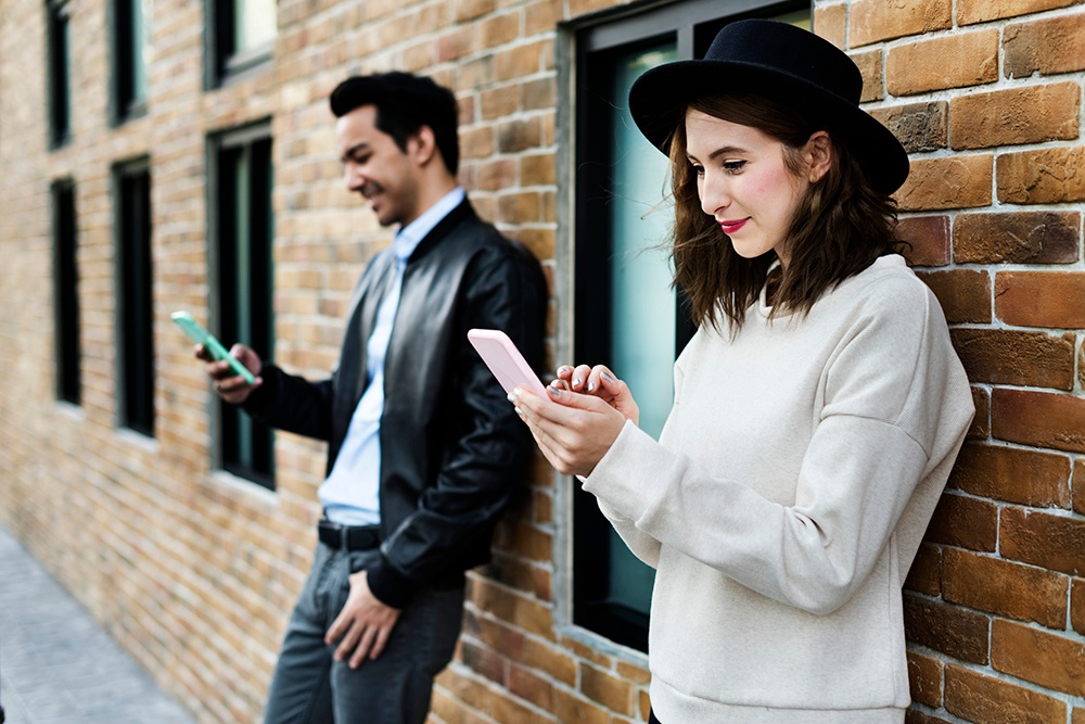 A male and female Weployee outside a building accepting their first Weploy Job on their phones