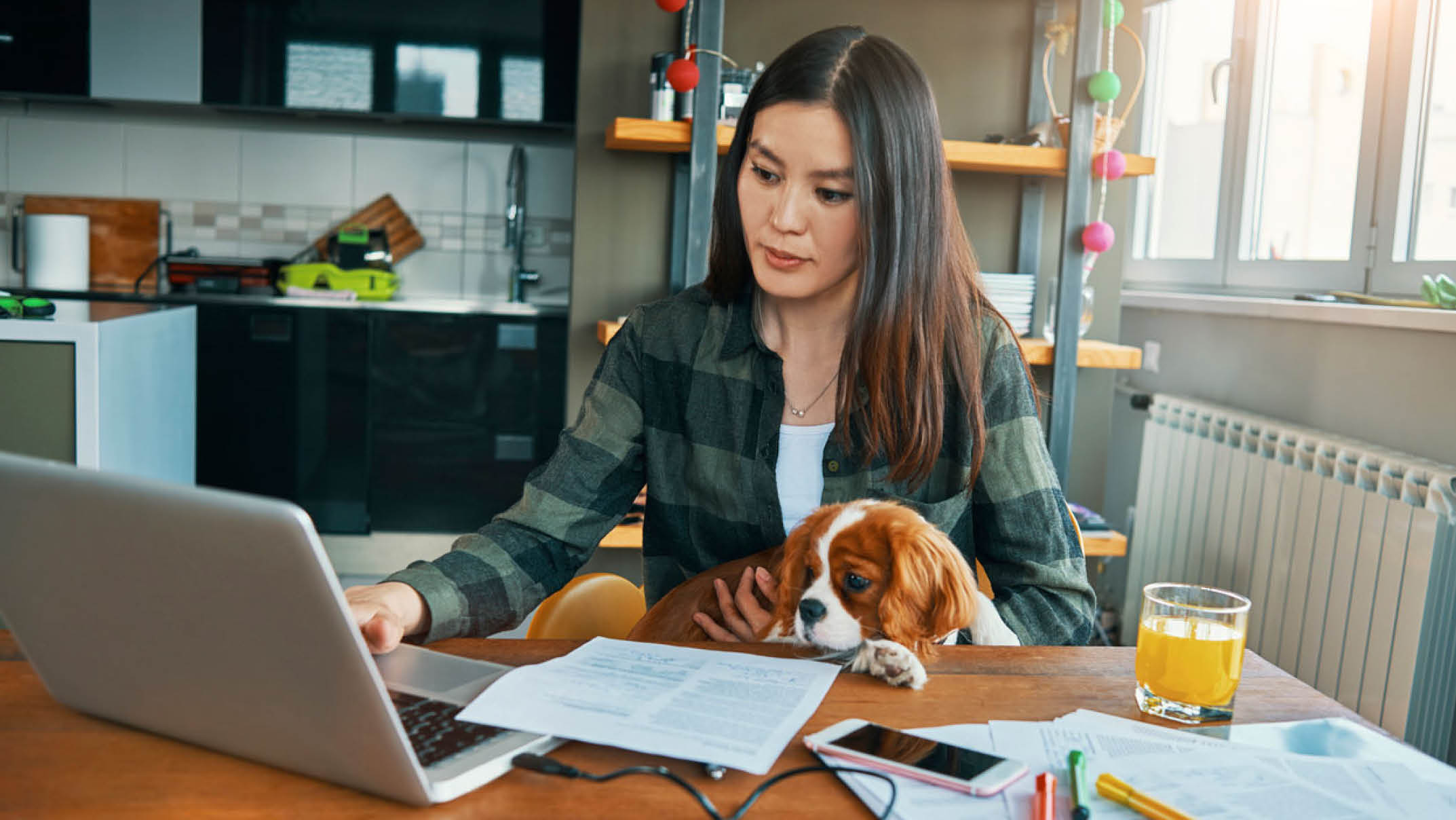 Female Working from Home with a Puppy on her Lap and on her Laptop