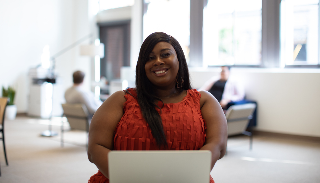 Happy job-seeker creating an ATS-friendly resume on her laptop