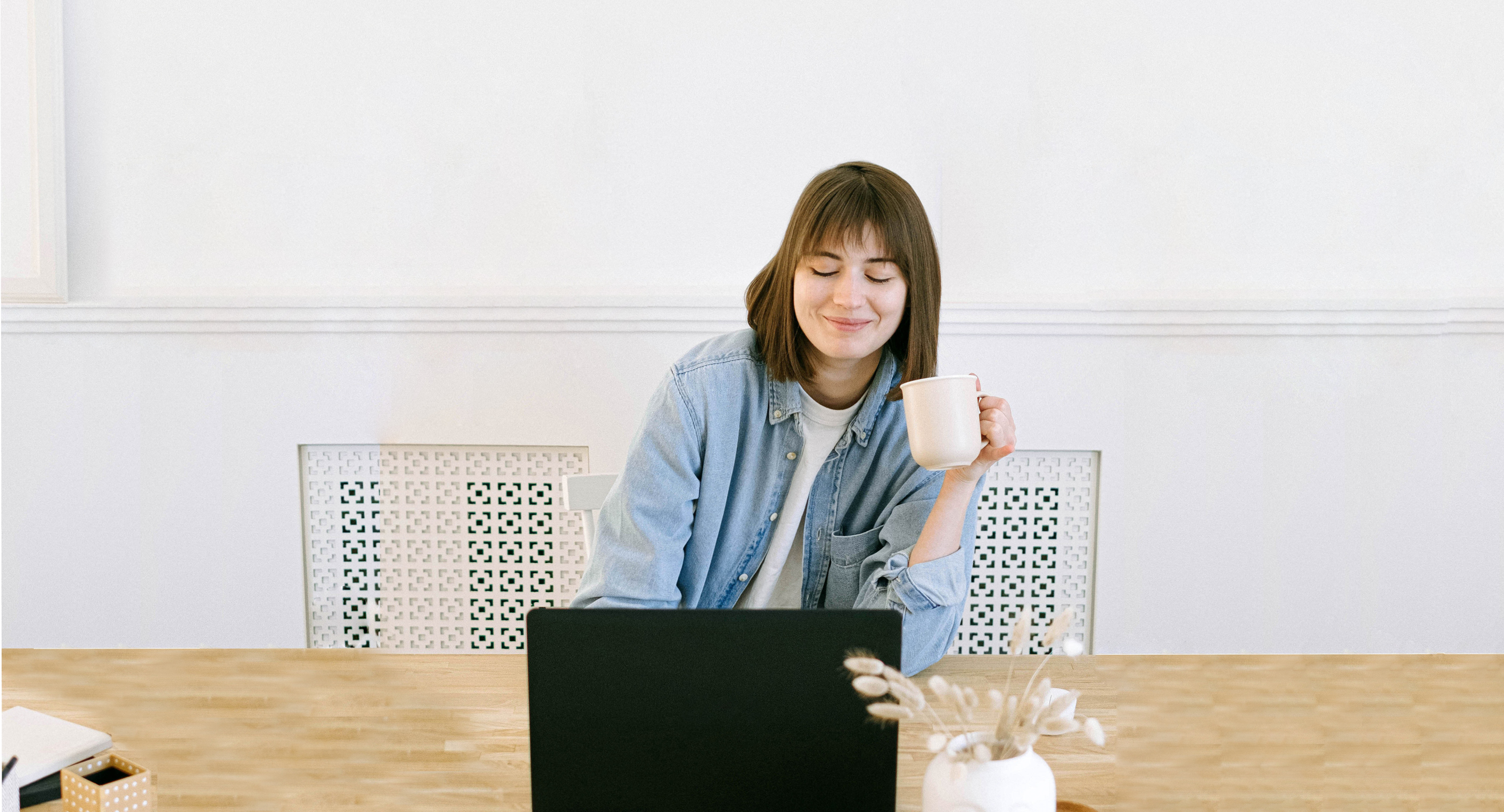 Female drinking coffee working on her laptop